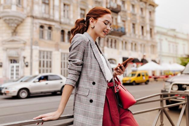 Donna dai capelli rossi in abito elegante in chat sul telefono