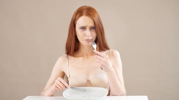 拒食症に苦しんでいる不健康な外観の赤髪の女性