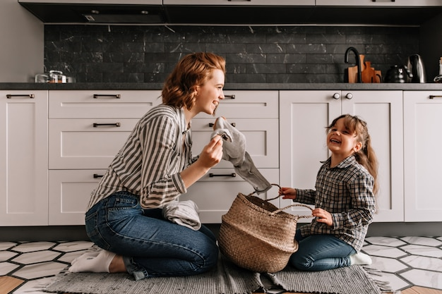 Red-haired woman tells jokes to her daughter and takes out dirty clothes from basket.
