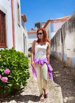 Red haired  woman walking in narrow streets in obidos