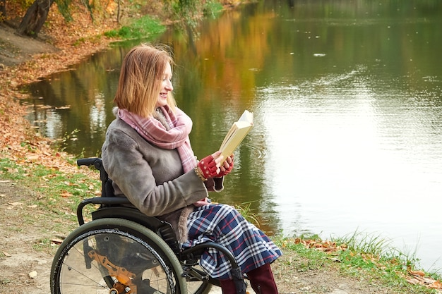 Red-haired woman in a wheelchair reading a book in the park on an autumn day