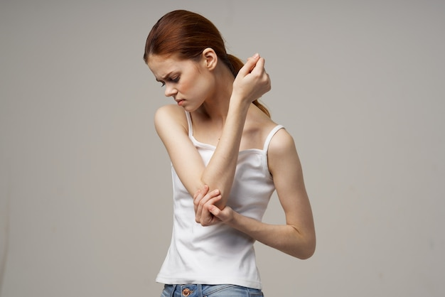 Red-haired woman in a white t-shirt on a beige background gesturing with her hands pain in the elbow