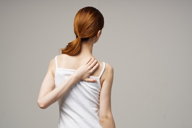 Red-haired woman in white t-shirt touching herself with hands on gray background cropped view