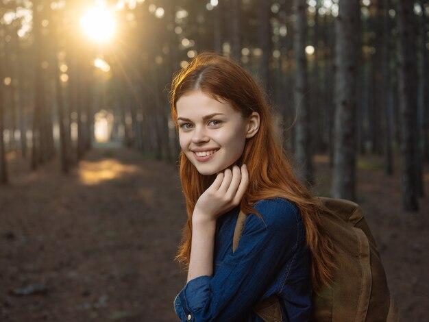 森の中で彼女の手に電話を持った赤毛の女性楽しい旅行。高品質の写真