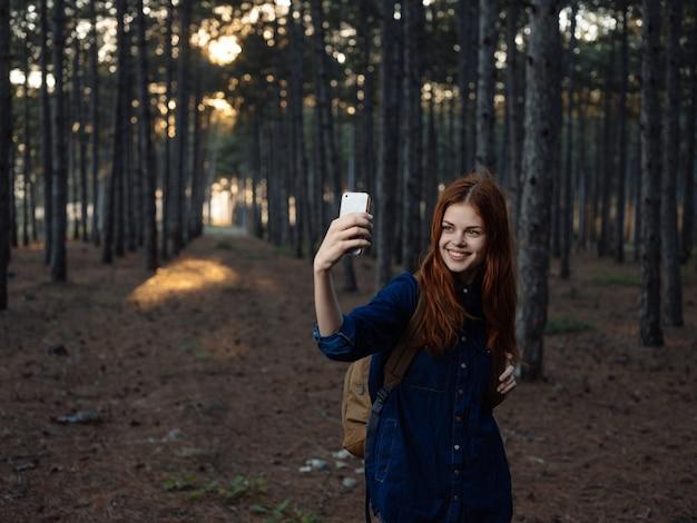 森の中で楽しい旅行で彼女の手に電話を持っている赤毛の女性。高品質の写真
