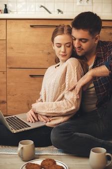 床のキッチンでノートパソコンを持っている間、彼女の恋人に抱かれてそばかすのある赤い髪の女性