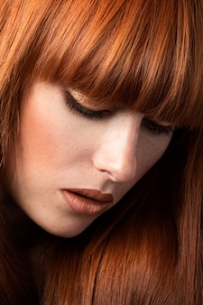 Red-haired woman with freckles looking down