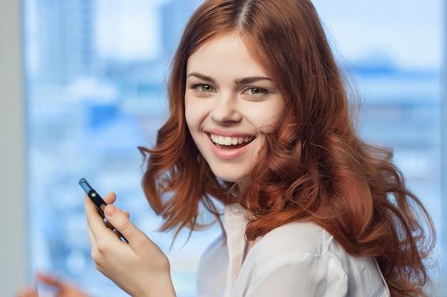 Рыжая женщина с телефоном в руках в профессиональном офисе технологий.