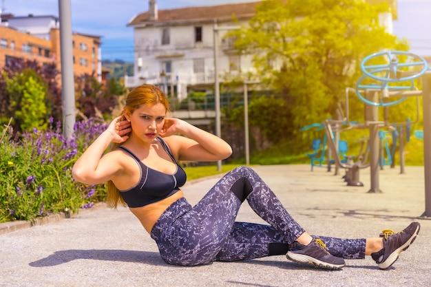 보라색 레깅스와 검은색 작업복을 입은 빨간 머리 여성은 기계 위에서 운동하고, 윗몸 일으키기를 하고, 도시에서 스포츠를 합니다.