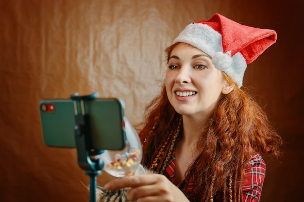 Red-haired woman with santa hat and dreadlocks clinks glass on smartphone. virtual talking with parents and using video chat. christmas video call.