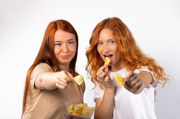 유리 그릇에 빨간 머리 여자 친구가 흰 벽에 감자 칩을 들고있다