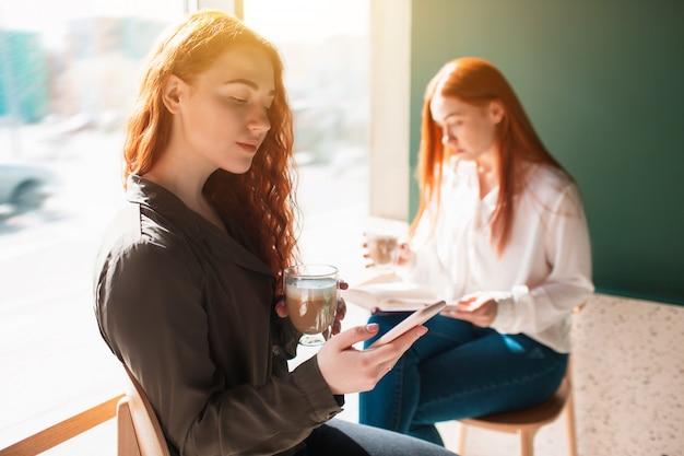 Рыжеволосые женщины смотрят на телефон. женские модели сидят у окна в кафе и пользуются мобильным телефоном.