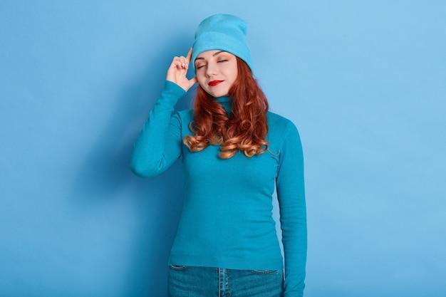 赤い髪の若い成人女性は顔を落ち着かせ、こめかみに人差し指を保ちます
