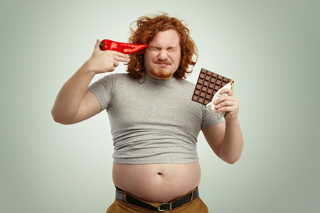 Red-haired young european bearded man wearing shrunk t-shirt with his stomach sticking out of jeans, holding bar of chocolate in one hand and red pepper at his temple, fed up with vegetable diet