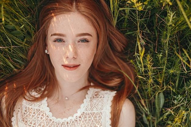 そばかすの笑みを浮かべて赤い髪の若い女性