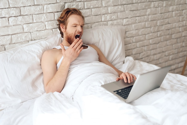 Red haired young guy works with laptop, yawning