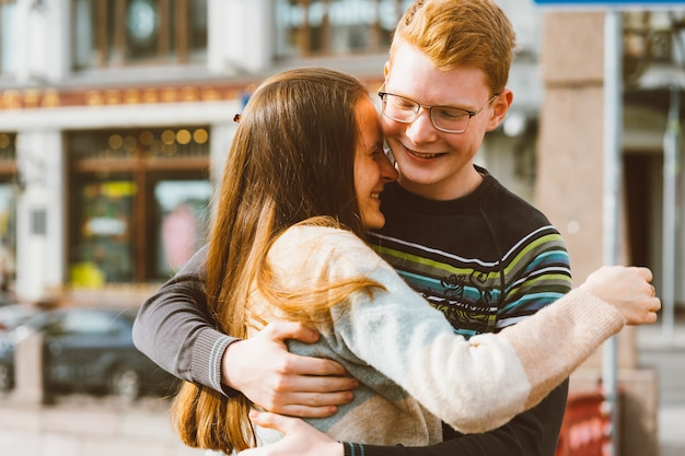 A red-haired young man embraces young woman with long dark hair, they laugh