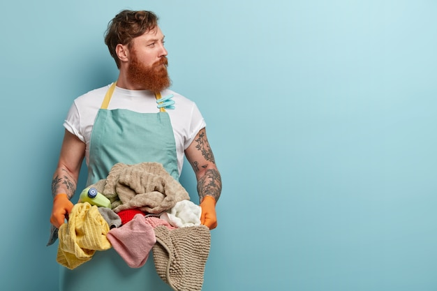 Red haired young man overstained with housekeeping, holds basin with pile of laundry, wears casual t shirt and apron, looks away, isolated over blue wall, has thoughtful look, focused away