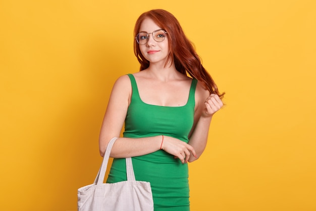 Red haired young woman in elegant green summer dress, holding eco bag, touching her beautiful red hair, standing against yellow wall