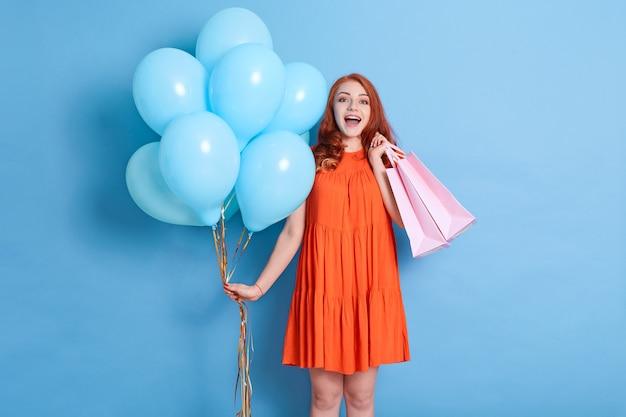Рыжая молодая женщина девушка в платье изолирована на синей стене