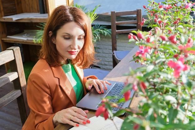 블레이저를 입은 빨간 머리의 젊은 여성이 노트북과 종이 다이어리가 있는 레스토랑의 열린 베란다에 앉아 있습니다. 사무실 밖에서 일하기, 프리랜서, 비즈니스 미팅 준비하기