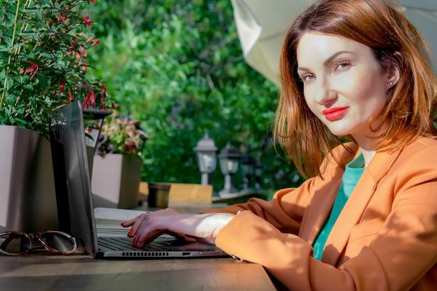 우아한 블레이저를 입은 빨간 머리의 젊은 여성이 노트북이 있는 카페의 열린 베란다에 앉아 있습니다. 사무실 밖에서 일하기, 프리랜서, 비즈니스 미팅 준비하기