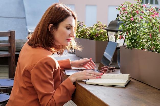 빨간 재킷을 입은 빨간 머리의 젊은 여성은 노트북이 있는 카페의 야외 테라스에 앉아 노트북에 메모를 합니다. 사무실 밖에서 근무, 프리랜서, 비즈니스 미팅 준비