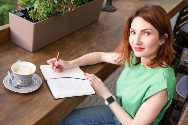 우아한 블레이저를 입은 빨간 머리의 젊은 여성은 커피 한 잔과 함께 카페의 개방형 테라스에 앉아 노트북에 메모를 합니다. 사무실 밖에서 근무, 프리랜서, 비즈니스 미팅 준비