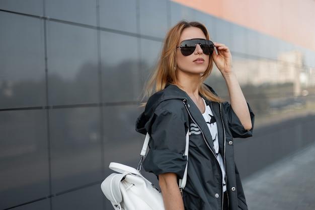 빈티지 가죽 배낭이 달린 세련된 재킷에 빨간 머리 젊은 여성이 서 있고 여름 날에 도시의 현대적인 건물 근처에서 유행 선글라스를 곧게 펴고 있습니다. 아주 아름다운 소녀.