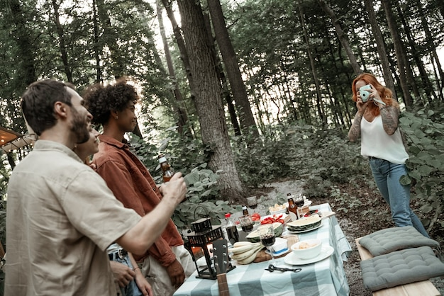 Red-haired young woman making polaroid photo of her friends on picnic, camping glamping life, resting with diverse friends outdoors, enjoying summer camping trip, having fun time in forest, copy space
