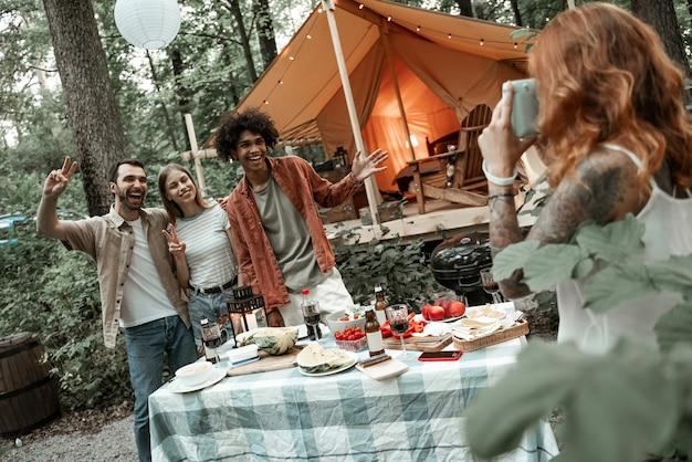 赤髪の若い女性がピクニックで友達のポラロイド写真を撮る、グランピングライフをキャンプする、屋外で多様な友達と休む、夏のキャンプ旅行を楽しむ、森で楽しい時間を過ごす、スペースをコピーする