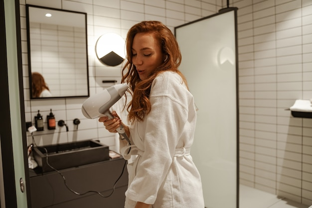 The red-haired young woman sings in the shower, she dreams with a hairdryer in her hands instead of a microphone.