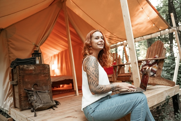 Рыжая молодая женщина с татуировкой, используя ноутбук возле глэмпинга палатки. отдых в кемпинге. малобюджетное путешествие, отпуск в лесу. wi-fi соединение, информационные коммуникационные технологии.