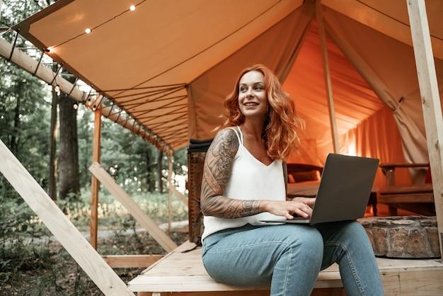 Рыжая молодая женщина с татуировкой работает удаленно на ноутбуке в глэмпинге. отдых в кемпинге. малобюджетный отдых, отдых в лесу. wi-fi соединение, информационные коммуникационные технологии.