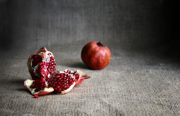 붉은 반 석류와 갈색 야 배경에 원시 석류. 소박한 스타일. 어두운 음식 사진.