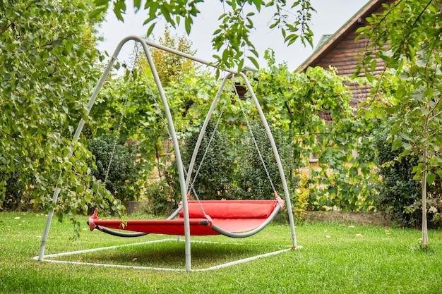통나무 집 코티지 근처 뒤뜰에 있는 녹색 잔디에 아무도 없는 금속 프레임의 빨간 해먹 스윙. 여름 정원의 해먹 그네에서 혼자 휴식을 취하세요.