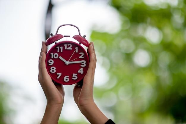 Красная рука и изображение будильника концепция пробуждения