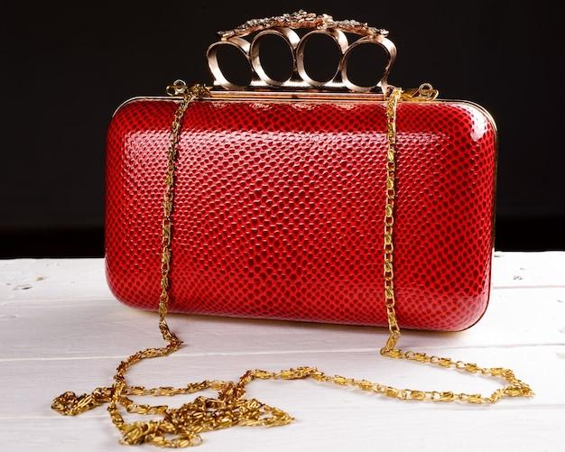 黒にペンブラスナックル付きの赤いハンドバッグクラッチ