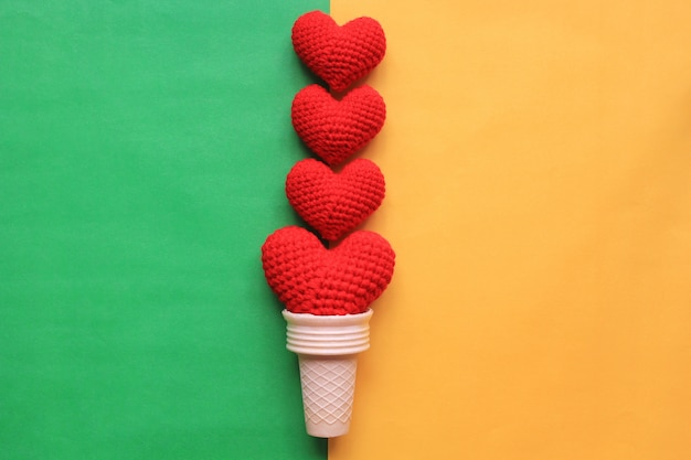 Red handmade crochet heart in waffle cup on colorful background for valentines day