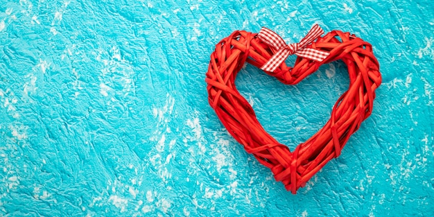 Red handmade heart on turquoise background, aqua color pattern with text space. flat lay with concept of love, valentine gift card, mockup. layout decoration. festive frame, art banner.