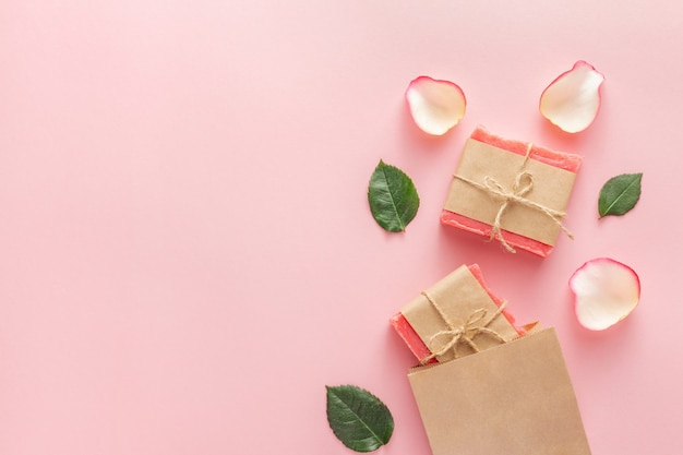 Красные кусочки мыла ручной работы в упаковке из крафт-бумаги на розовом
