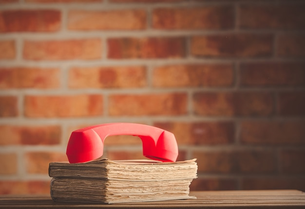 Red handset over old books on wooden table