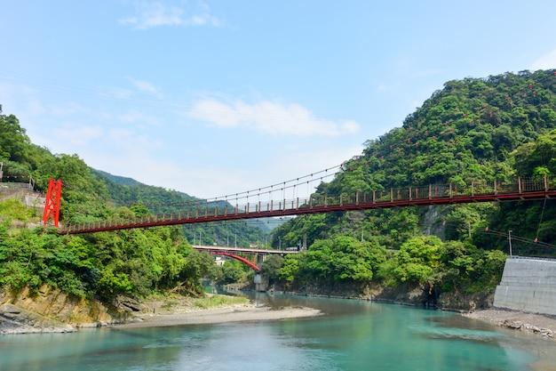 Red hanging bridge above river