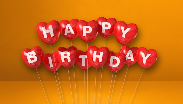 Red happy birthday heart shape air balloons on orange background scene. horizontal banner. 3d illustration render