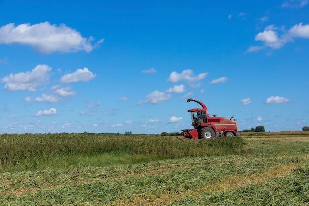 田舎の畑の赤い収穫機。晴れた夏の日の穀物収穫の概念、側面図。