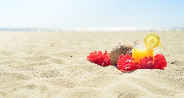 Red hawaiian lei garland with orange juice in a jar on the beach