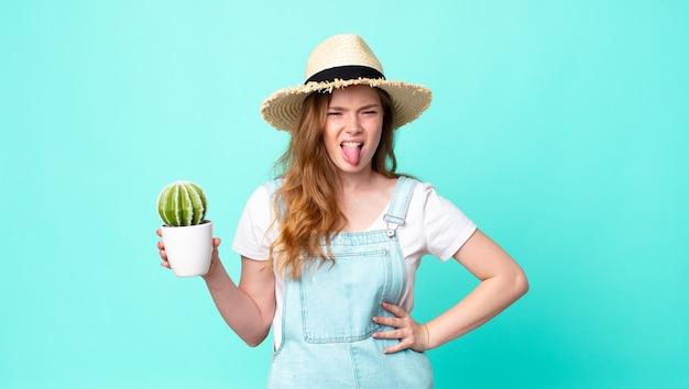 Рыжая красивая женщина-фермер чувствует отвращение и раздражение, высовывает язык и держит кактус