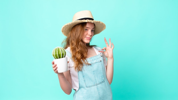 Red head pretty farmer woman looking arrogant, successful, positive and proud and holding a cactus