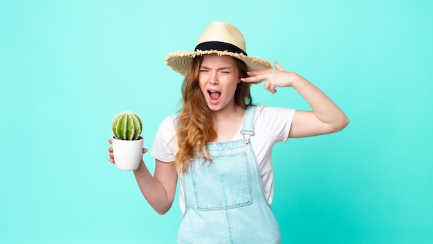 Red head pretty farmer woman looking unhappy and stressed, suicide gesture making gun sign and holding a cactus