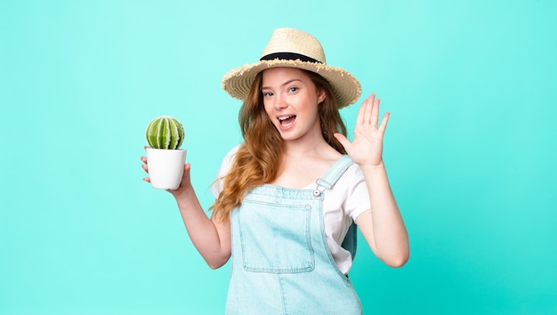 赤毛のかわいい農家の女性が笑顔でフレンドリーに見え、5番を示し、サボテンを持っています